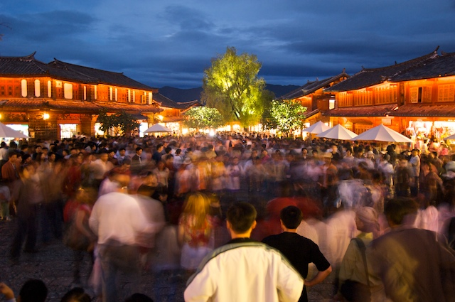 People dancing in two large circles in Lijiang, China's town square.